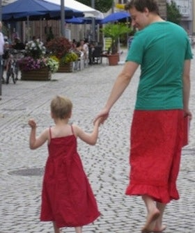 father-of-the-year-helps-dress+wearing-son-feel-comfortable-by-putting-on-a-skirt-himself